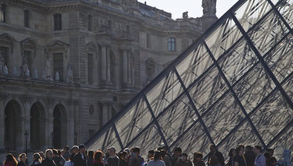 Tourists line up to enter the Louvre museum in Paris,