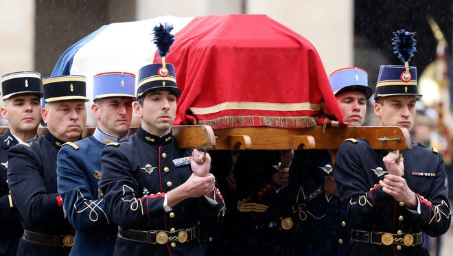 French Republican Guards and cadets from the joint-army military school (Ecole Militaire Interarmes, EMIA) carry the coffin of late Lt. Col. Arnaud Beltrame during a national ceremony for Beltrame, on March 28, 2018 at the Hotel des Invalides in Paris.