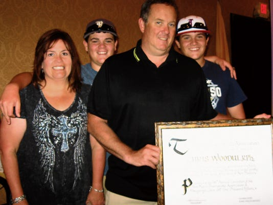 Chris Woodul accepts his award with family looking on.