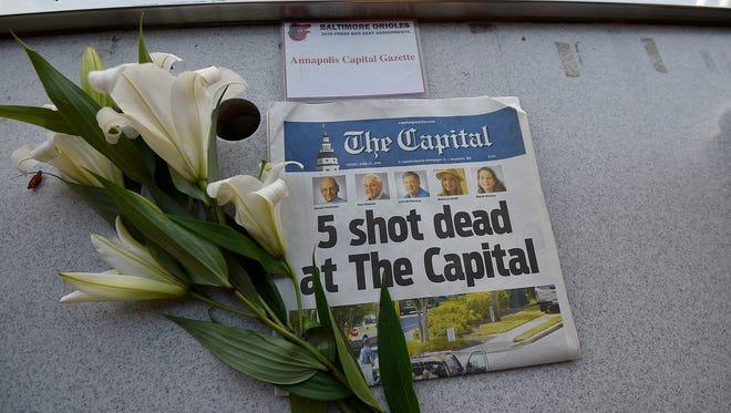A memorial for Capital Gazette sports writer John McNamara is displayed at a seat in the Camden Yards press box.