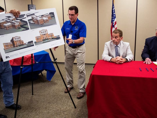 Tyner Little, who handles governmental affairs for Nueces County, reveals plans for the old courthouse before Steve Goodman, managing principal with Improvement Network Development Partners LLC, and Nueces County Judge Loyd Neal participate in a contract signing on Thursday, May 24, 2018. The deteriorating courthouse will be turned into a hotel.