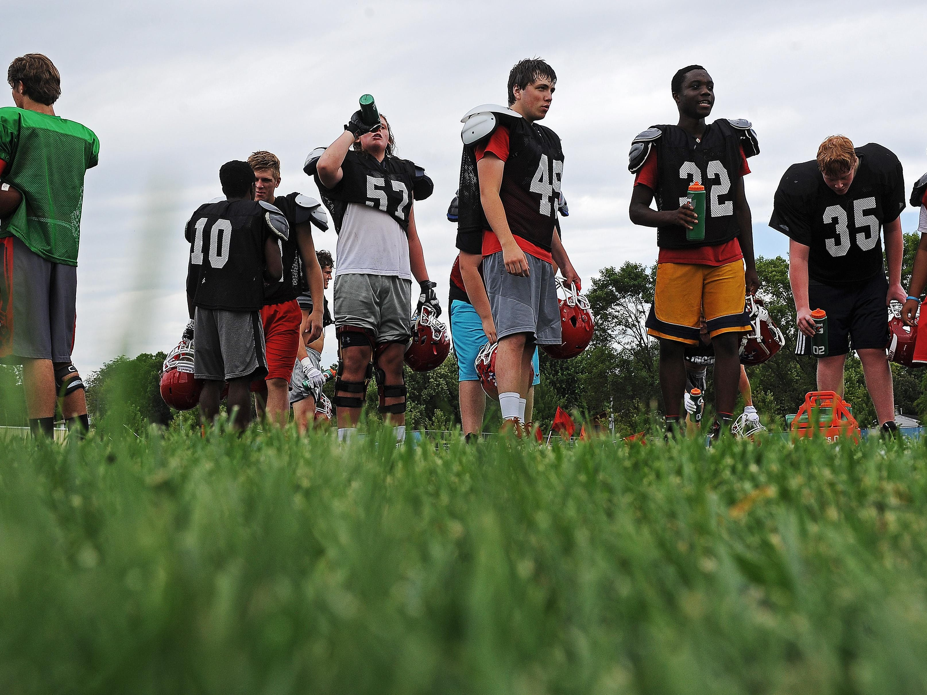 Lincoln High School football players get a drink during a Lincoln High School football practice Thursday, Aug. 11, 2016, at Lincoln High School in Sioux Falls.