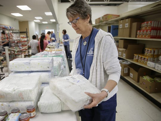 Joanie Reuss organizes diapers by their size for distribution June 11 at St. Joseph Food Program in Menasha. Diapers are distributed to local food pantries through the Fox Cities Diaper Bank.