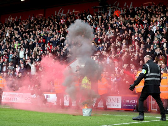 A flare is extinguished, during the English Premier League soccer match between Bournemouth and Southampton, at the Vitality Stadium, in Bournemouth, England, Sunday Dec. 3, 2017. (Adam Davy/PA via AP)