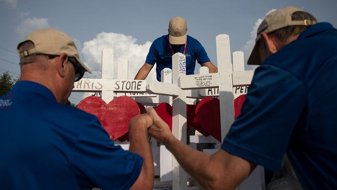 Members of the Billy Graham response team and Crosses for Losses's Greg Zanis pray over ten crosses for the victims of the Santa Fe High School shooting out side the school on May 21, 2018.  Last Friday, 17-year-old student Dimitrios Pagourtzis entered the school with a shotgun and a pistol and opened fire, killing 10 people.