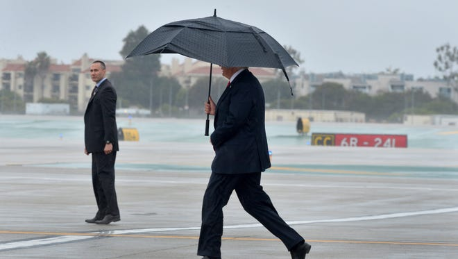 President Donald Trump walks across the tarmac at Los Angeles International Airport on Tuesday as rain fell during his visit to California.