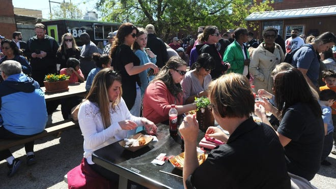 Nellie Doneva/Reporter-News People eat at picnic tables while others wait in line at the food truck event.