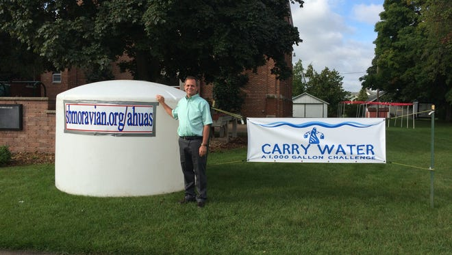 Rick Nelson stands with the 1,000-gallon holding tank that water will be carried to on the 19th to raise money for a Honduran hospital where he is doing ministry work.