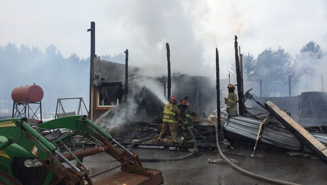 Firefighters spray water on the remains of a maintenance garage at Lake State Lawn & Landscaping on Columbia Highway in Eaton Rapids Township.