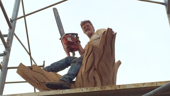 Chainsaw artist John Birch sits perched upon one of his latest creations