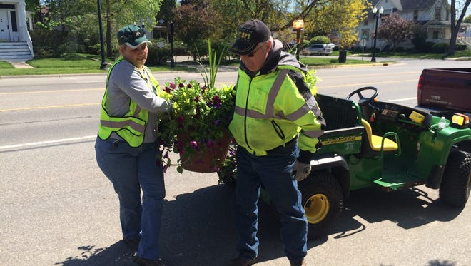 City of Howell workers Robin Edmonds and Greg Tanner unload a small flower pot Wednesday.