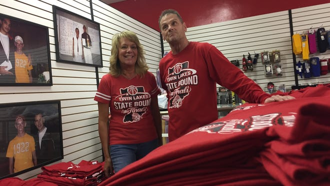 Tammy and Mickey Belt, owners of Mickey B's in downtown Monticello, take a break among the stacks of T-shirts commemorating Twin Lakes basketball team's trip to the Class 3A state finals game Saturday. The couple had so many orders for shirts that they had to close the store to customers so they could concentrate of printing in time for a Friday afternoon pep rally at the high school.