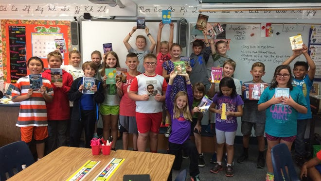 Riverside fourth-graders show off the new books their classroom received, thanks to the James Patterson Partnership Giveaway.