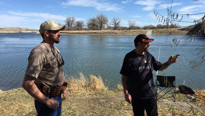 Brett Logan, a game warden with Montana Fish, Wildlife and Parks,  chats with fisherman Marty Redfern of Great Falls along the Missouri River at the Ulm Bridge in 2015. As a result of funding changes, game wardens will be spending more time on wildlife management related tasks and less time on traditional law enforcement duties such as checking fishing and hunting licenses, according to FWP.