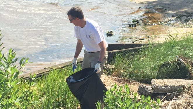 Gov. Ralph Northam picks up trash along Cape Charles Harbor during a Clean the Bay event in Cape Charles, Virginia on Saturday, June 2, 2018.