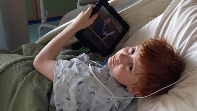 Ben Brewer, 13, of Aurora, Colo., plays a video game as he stays in isolation during his cancer treatment.