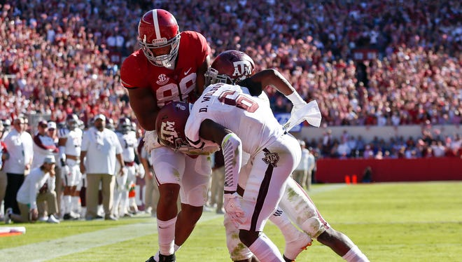 Alabama tight end O.J. Howard, left, scores a touchdown against Texas A&M defensive back Donovan Wilson, front, and Texas A&M linebacker Otaro Alaka during the first half of an NCAA college football game, Saturday, Oct. 22, 2016, in Tuscaloosa, Ala. (AP Photo/Brynn Anderson)