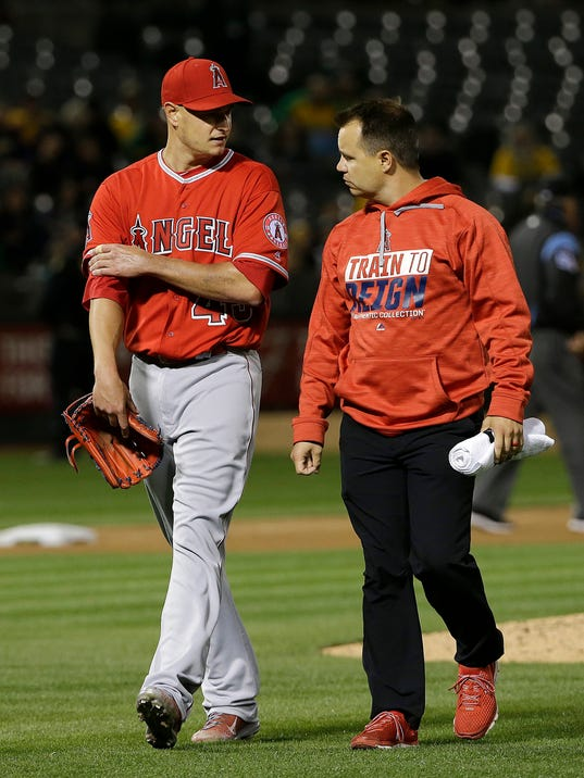 FILE - In this April 5, 2017, file photo, Los Angeles Angels pitcher Garrett Richards, left, leaves the field with a trainer after being relieved during the fifth inning of the team's baseball game against the Oakland Athletics in Oakland, Calif. Richards pitched April 5, then not again for the Angels until Sept. 5, going through an entire throwing program again to regain arm strength and stamina. He made only six starts in each of the past two years, limited in 2017 by an irritated nerve in his biceps that cost him most of the season. (AP Photo/Jeff Chiu, File)