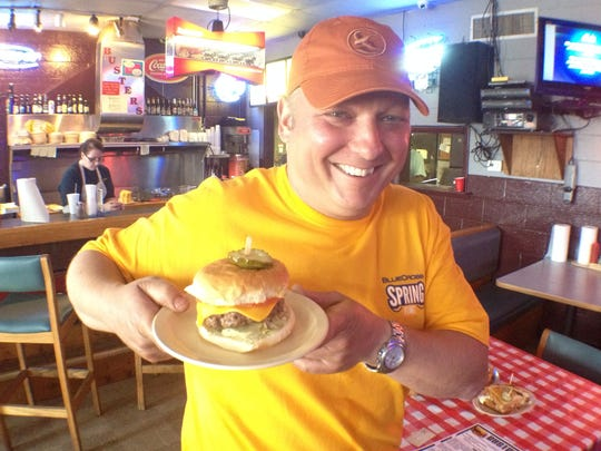 Buster's Place owner Peter Moret holds up a Buster Burger.