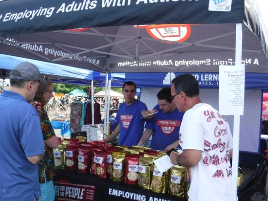 Popcorn For The People Director of Operations, Offsite Fundraising Steve Frank (right) looks on as Joseph (center) an employee with Asperger's syndrome, serves two patrons with Alex Frank (left), who also helped sell the nonprofit's popcorn during the festival.