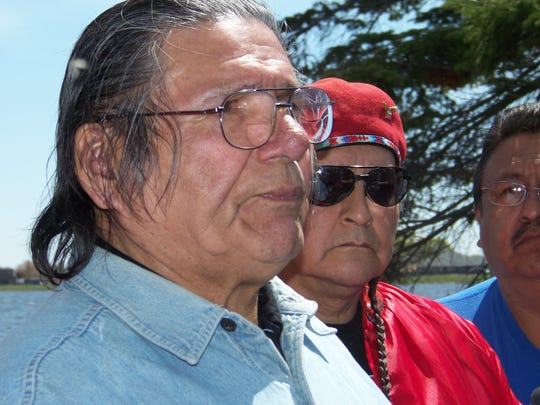 In this May 14, 2010, file photo, American Indian activist Dennis Banks, left, speaks to reporters on Lake Bemidji, during an American Indian treaty rights protest in Bemidji, Minn. The family of Banks says he died Sunday, Oct. 29, at the age of 80. Banks was a co-founder of the American Indian Movement and a leader of the Wounded Knee occupation in 1973.