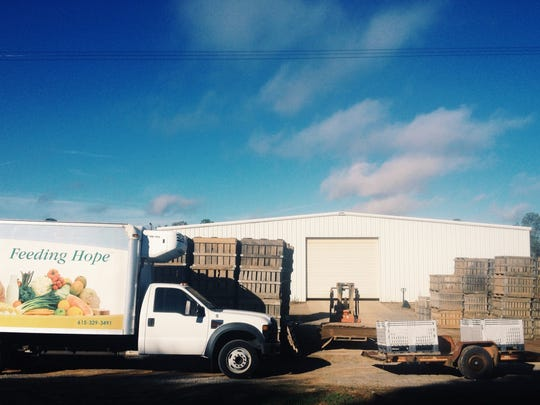 A Second Harvest delivery truck parks near palates of rescued sweet potatoes.