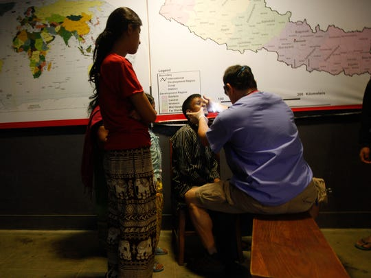 Physician assistant Bernie Racey examines a protrusion on the nose of a patient. Medical staff from the Delaware Medical Relief Team saw more than 300 patients during a clinic at Khwopa Higher Secondary School in Bhaktapur, Nepal, on Saturday.