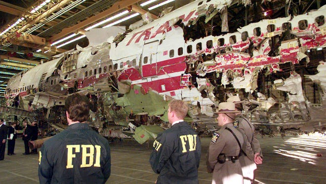 In this Nov. 19, 1997,  photo, FBI agents and New York State Police guard the reconstruction of TWA Flight 800 in Calverton, N.Y. Flight 800 exploded and crashed July 17, 1996, while flying from New York to Paris, killing all 230 people aboard.