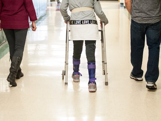 Brooke Hopkins walks with her mother and father before her parents leave her for that half-day at school that she is able to do as her recovery continues.