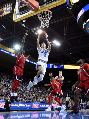Lonzo Ball of the UCLA Bruins scores a basket against Kadeem Allen of the Arizona Wildcats during the first half of the game at Pauley Pavilion.