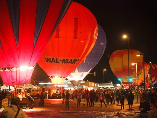 Hot air balloons line Lake Powell Boulevard and fire their burners to light up the night skies during the balloon glow Saturday, Nov. 2, 2013 in Page, AZ..