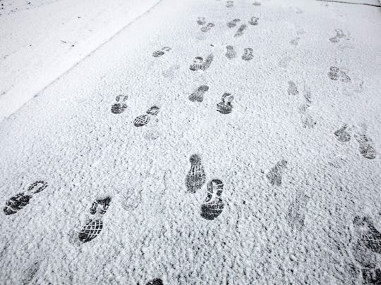 Footprints left by runners competing in the Expedition St. George, a 50 mile team really race that winds from the Town Square Park in downtown St. George, up through Snow Canyon State Park, through Washington Fields and back around the Southern Parkway to the Dixie Center, can be seeing the trail along state Route 18 Saturday, Dec. 7, 2013. Despite the cold and wintery conditions, 42 teams, most comprised of five team members, competed in the relay race.