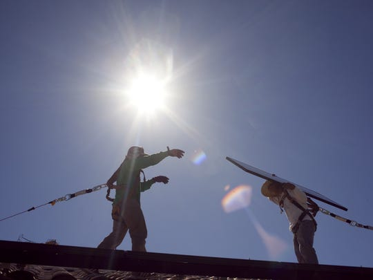SolarCity employees work on the rooftop of a north