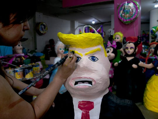 "Alicia Lopez Fernandez paints a pinata depicting Donald Trump at her family's store ""Pinatas Mena Banbolinos"" in Mexico City."
