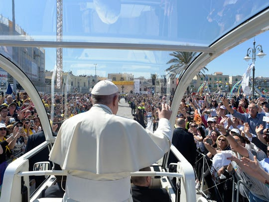 Pope Francis greets the crowd to celebrate a mass in