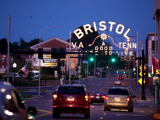 As night falls, traffic makes it way east on State Street in downtown Bristol. On the left side of the road is Virginia and Tennessee is on the right.
