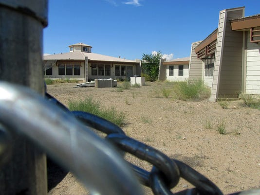 The Home for Women and Children in Shiprock is seen through a locked gate on Thursday. The gate around the unopened domestic violence shelter is lined with barbed wire, and sections are tagged with graffiti.