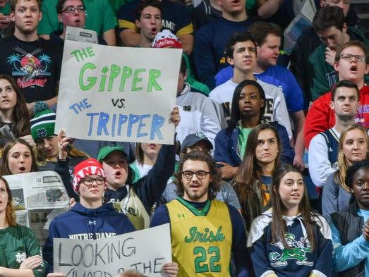The Notre Dame student section holds signs referencing