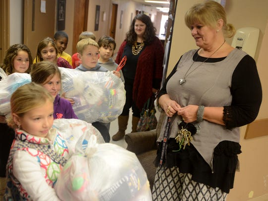 Gail Gustafson receives bags of new socks from Median Middle School fourth-graders Tuesday for Kid President's Socktober initiative.