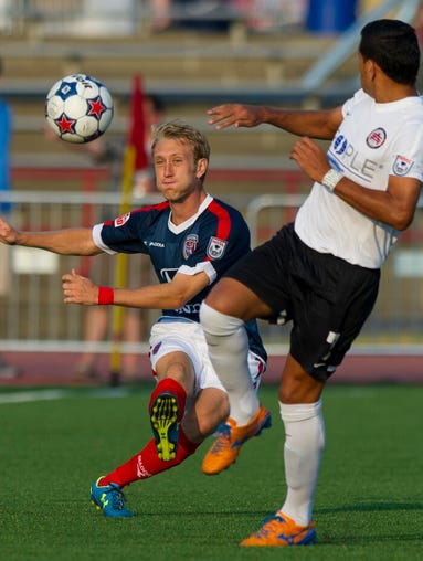 Indy Eleven's Brad Ring (4) fires a pass past the defense of Atlanta's Junior Sandoval (7) during the first half of action. Indy Eleven hosted the Atlanta Silverbacks in NASL soccer action, Saturday, August 2, 2014, at Michael A. Carroll Track and Soccer Stadium .