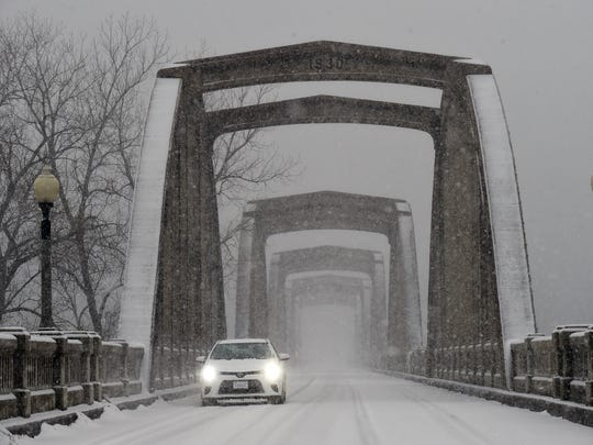 A vehicle travels across the R.M. Ruthven Bridge in Cotter on Wednesday. Winter Storm Thor moved through the area Wednesday leaving roads covered in ice and snow.