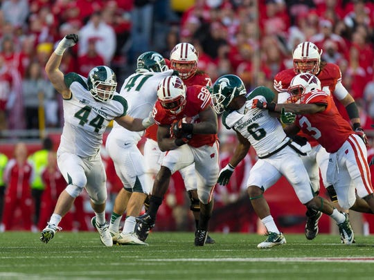Former MSU players Mylan Hicks (6) and Marcus Rush (44) close in on Wisconsin Badgers running back Montee Ball (center) during the Spartans' game in Madison in 2012. Hicks was shot and killed Sunday in Calgary, where he played for the CFL's Stampeders.