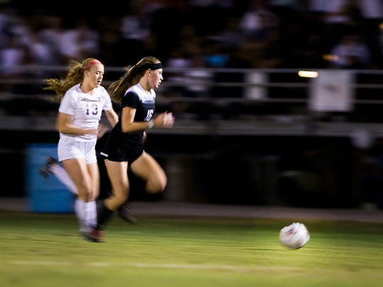 Estero junior, Maggie Struble, and Archbishop McCarthy sophomore, Kelly Hastings, chase the ball down the field during the class 4A state semifinal against Archbishop McCarthy High School on Friday, February 16, 2018 at Estero High School.
