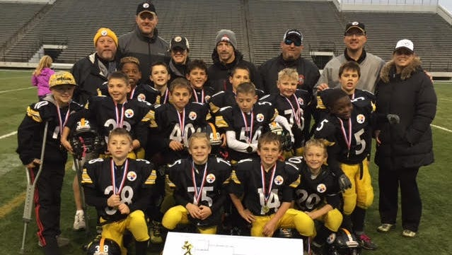 The MYFCC champion Plymouth-Canton Steelers Junior Freshman team celebrates an undefeated season. In the first row (from left) are LJ Kerul, Ben Papke, Lucas Diton and Micky Laser. In the second row (from left) are Kyle Candito, Logan Rozum, Sam Nieset, Kendon Dmytrusz and Jayden Buckines. In the third row (from left) are Bryson Williams, Mitchel Paspal, Drew Eisenbeis, Mack Swafford, Isaac Plave and Dominic Allam. In the fourth row (from left) are head coach Dan Cosgrove, Coach Balow, Team Mom Papke, Coach Kerul, Coach Laser, Coach Diton and Team Mom Eisenbeis. Not pictured is player Akshay Singh.