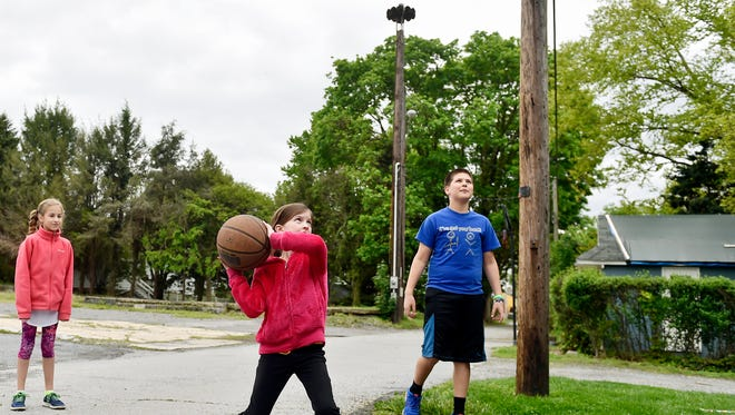 Olivia Feltenberger, 10, left, and Ethan Nikolaus, 13, right, watch as Macy McNatt, 9, attempts a basket about 30 yards away from a siren in an alley off North Fourth Street in Wrightsville. Some borough residents say they are concerned about the impact on their families' hearing. Other residents and the Wrightsville fire department say the sirens are the most reliable way to alert firefighters to emergencies.