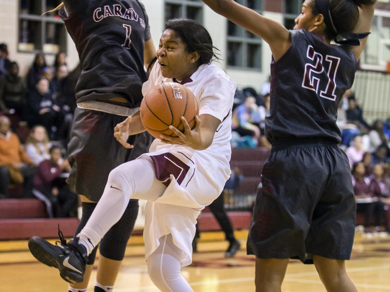 Concord's Jamiyah Dennis puts up a shot as she ducks between Caravel's Ondia Brown (No. 1) and Kaylee Otlowski (No. 21) in the first half of Caravel's 42-26 win over Concord at Concord High School on Monday night.