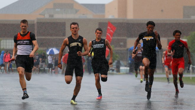 Runners compete in the 800 meter relay in a downpour during the Honor Roll track meet Tuesday at Holt High School.