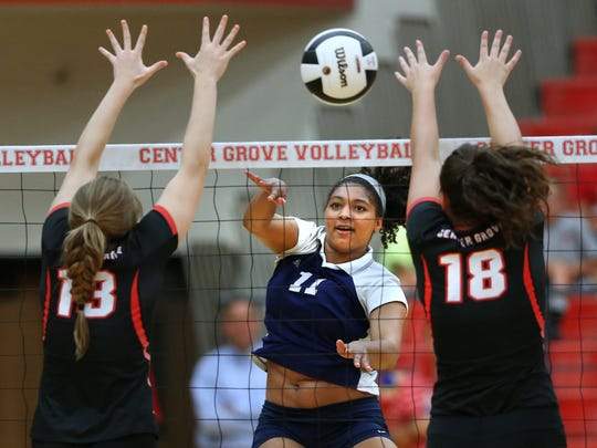 Cathedral's Nia Robinson spikes the ball through Center Grove's Malea Howie, left, and Tonia Rumble during their match held at Center Grove High School on Tuesday, August 25, 2015. Cathedral pulled off the win in the 5th set.