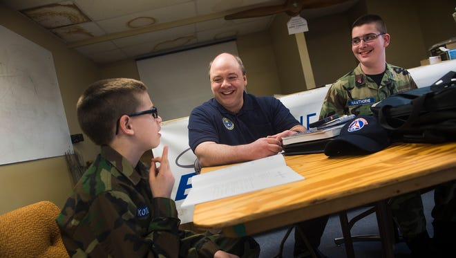 Griffith Kotlinski, 12, left, of Gettysburg, Air Space educator Rob Clark, center, and Alex Hawthorne, 13, of New Oxford go over aerospace materials at Gettysburg Airport. Kotlinski and Hawthorne are cadets in the Gettysburg squadron of the Civil Air Patrol.