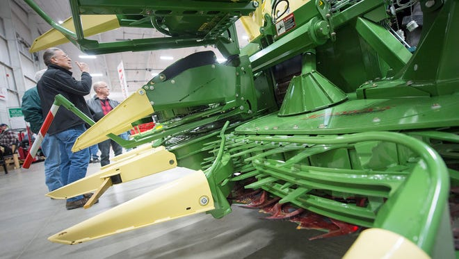 Jay Shaub, of Lititz, who was in fleet services for the egg industry for 30 years, looks over a folded eight row corn chopper at the Keystone Farm Show. The corn chopper is folded for row transport and is used to harvest corn.